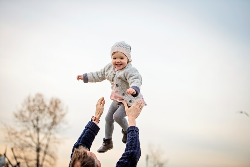 Family Photography, father throwing little girl into the air