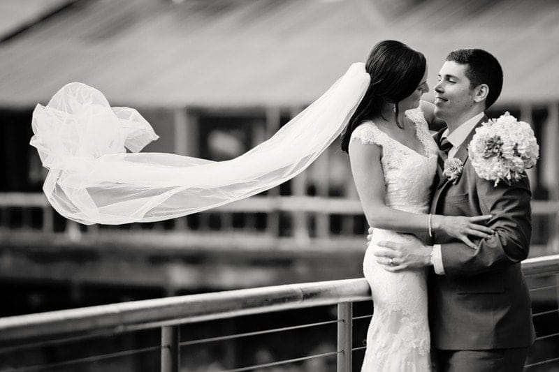 Wedding Photography, black and white of couple with veil flying in the wind
