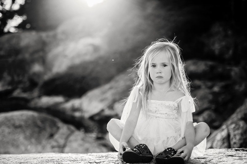 Family Photography, black and white of little girl sitting on the ground with rocks in the background