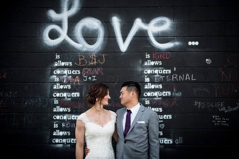 "Wedding Photography, bride and groom standing in front of ""Love"" graffiti brick wall"