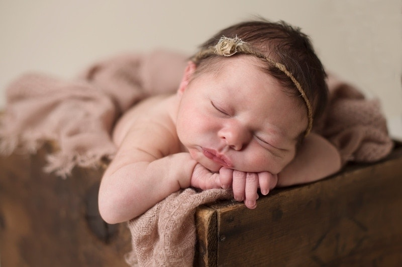 Baby Photography, baby asleep leaning on the edge of a wooden crate