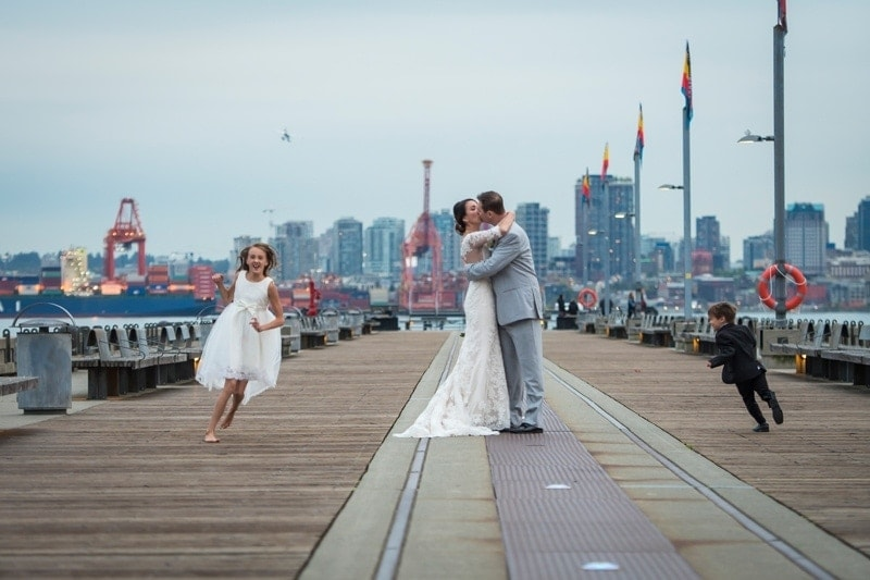 Wedding Photography, couple kissing on pier with kids running around them
