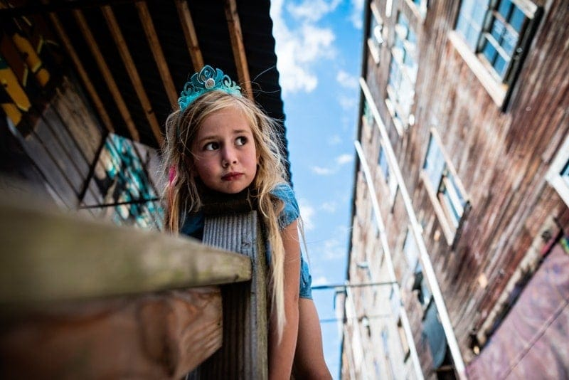 Family Photography, little girl laying on handrail wearing a blue crown