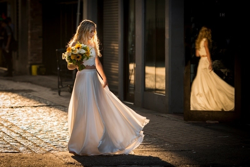 Wedding Photography, bride holding a yellow and white bouquet next to a window with her reflection in it