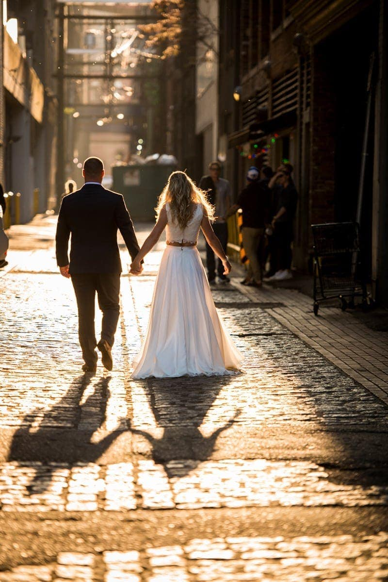 Wedding Photography, bride and groom walking down an alleyway