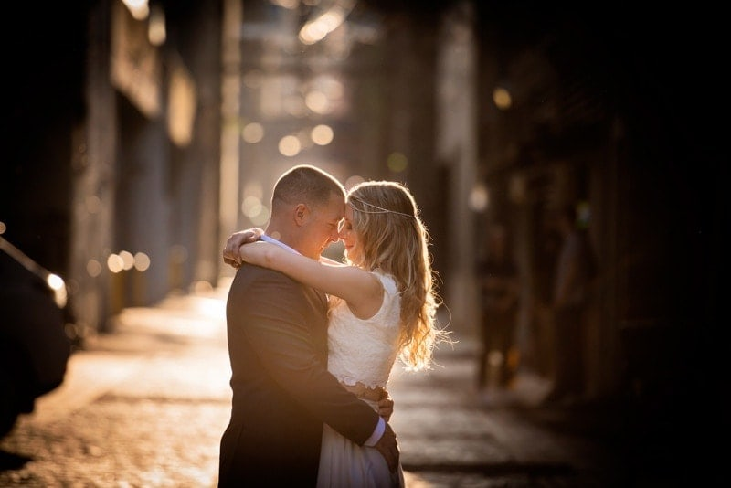 Wedding Photography, couple with their arms around each other down an alleyway