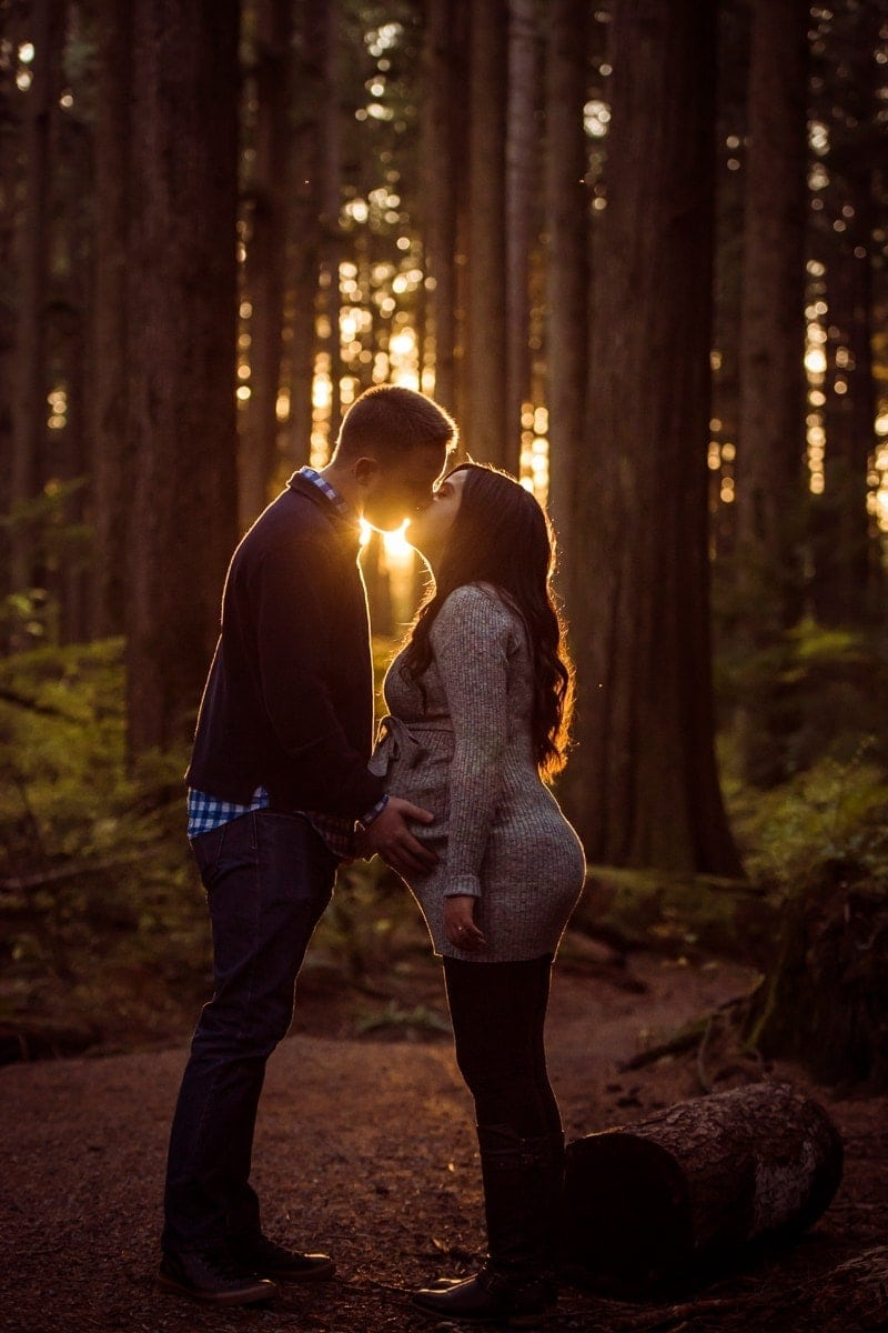 Family Photography, man and pregnant woman kissing in forest