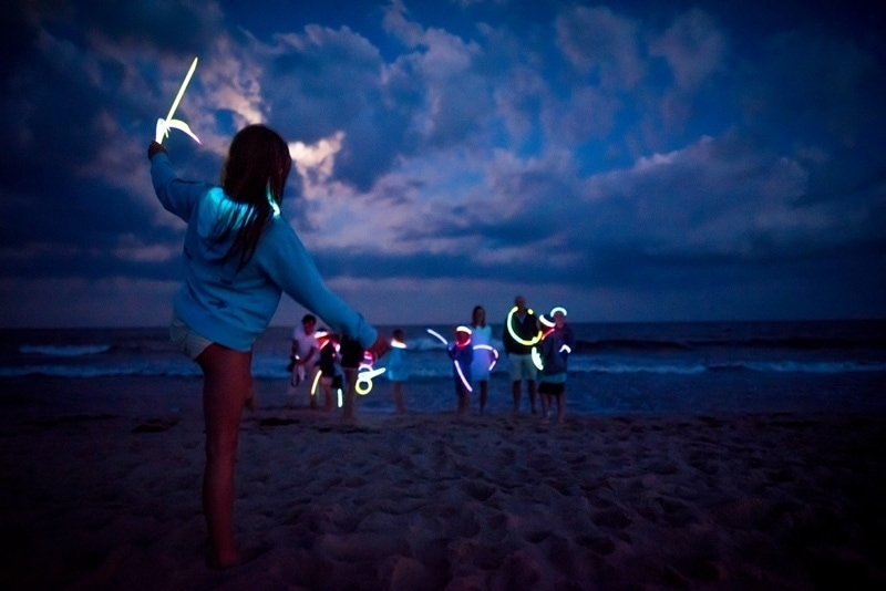 Family Photography, family with children playing with glow sticks at the beach