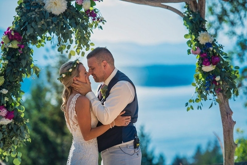 Wedding Photography, couple about to kiss under a floral archway