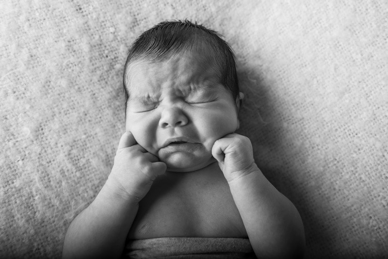 Baby Photography, black and white of baby with its hands under their cheeks