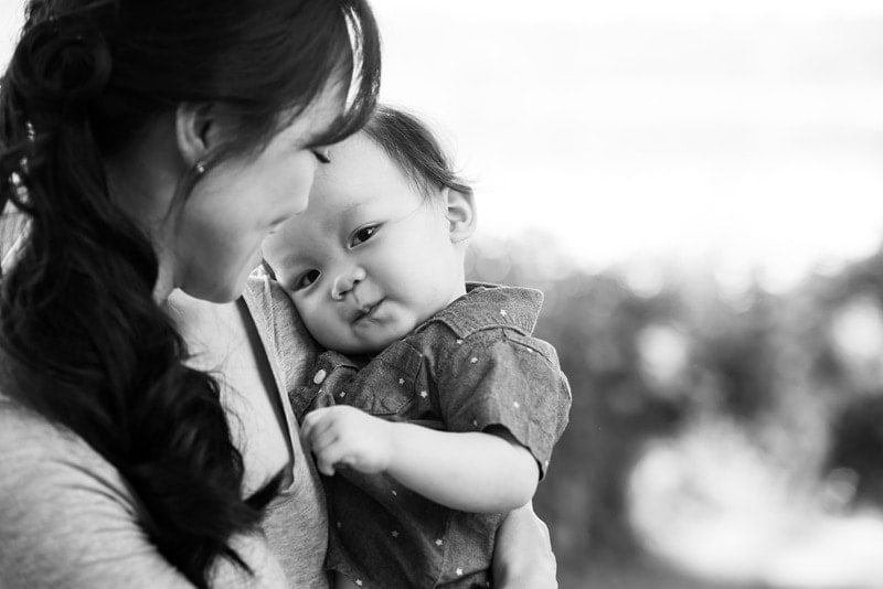 Family Photography, black and white of mother holding up baby and looking at him