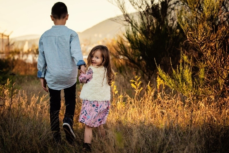 Family Photography, brother holding young sisters hand walking through tall grass