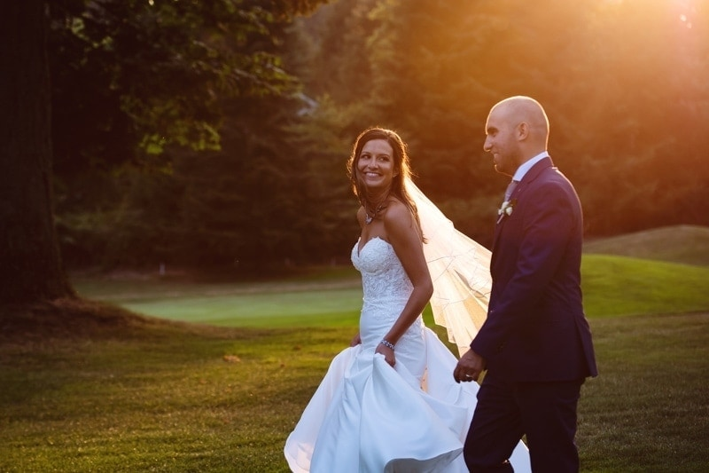 Wedding Photography, couple walking through the grass at sunset