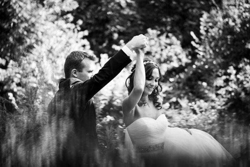 Wedding Photography, black and white of bride and groom dancing in tall grass