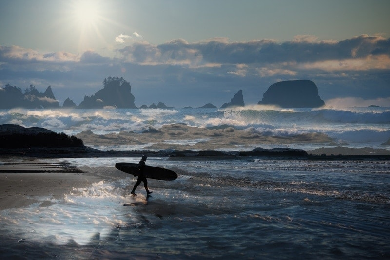 Family Photography, wide angle shot of surfer walking into the water