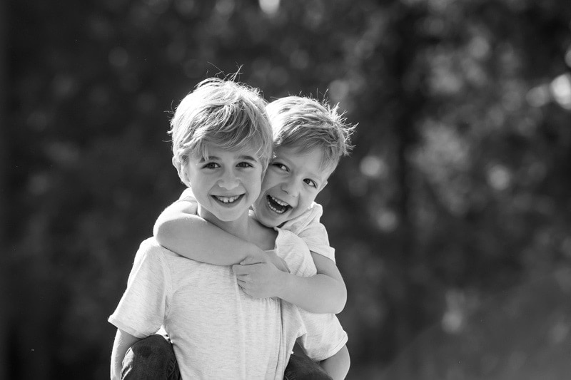 Family Photography, older brother giving little brother a piggyback ride