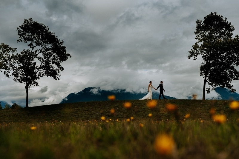 Wedding Photography, couple walking along a hillside in the distance