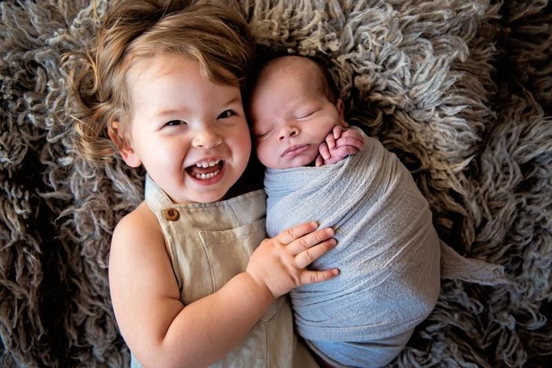 Vancouver Photo studio, little sister hugging newborn baby