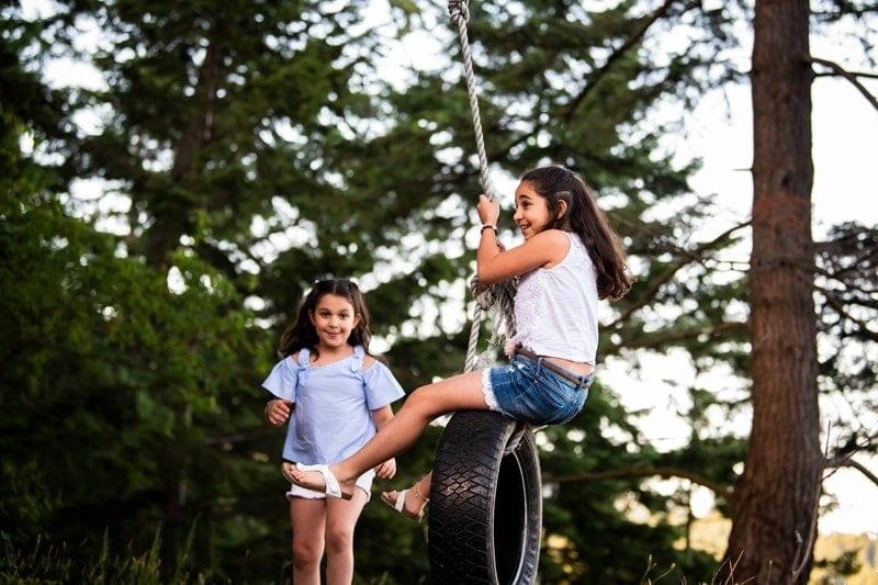 Family Photography, two girls playing with a tire swing