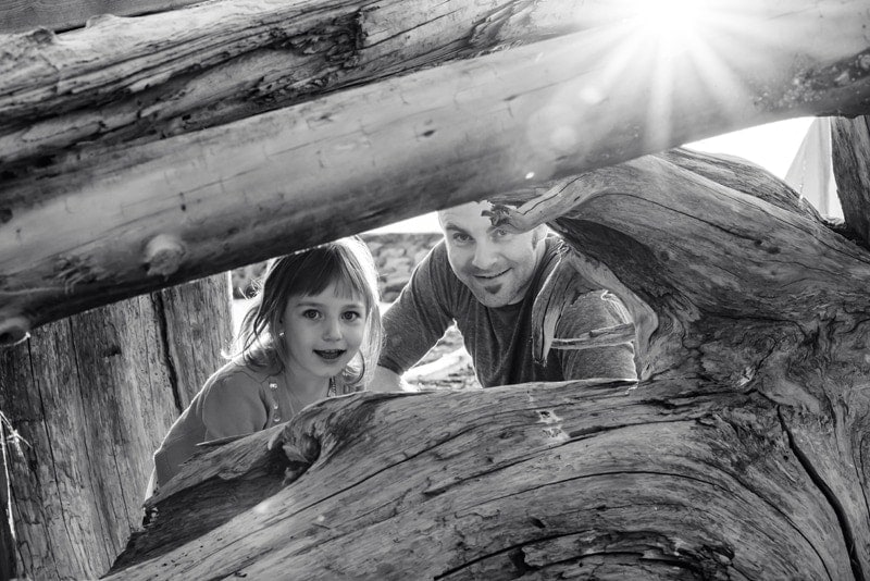 Family Photography, father and daughter looking through large logs on the beach