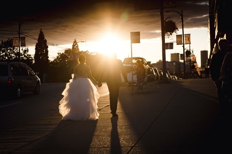 Wedding Photography, couple walking down a street, toward the sunset