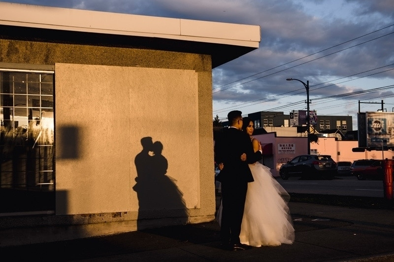 Wedding Photography, couple holding eachother casting a shadow on the wall behind them