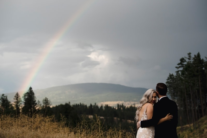 Wedding Photography, couple standing together with husband looking at a rainbow in the distance