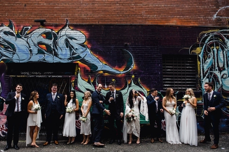 Wedding Photography, bridal party posing in front of urban painted brick wall