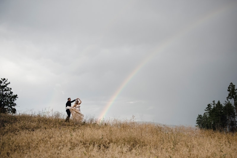 Wedding Photography, couple dancing in field with a rainbow in the background