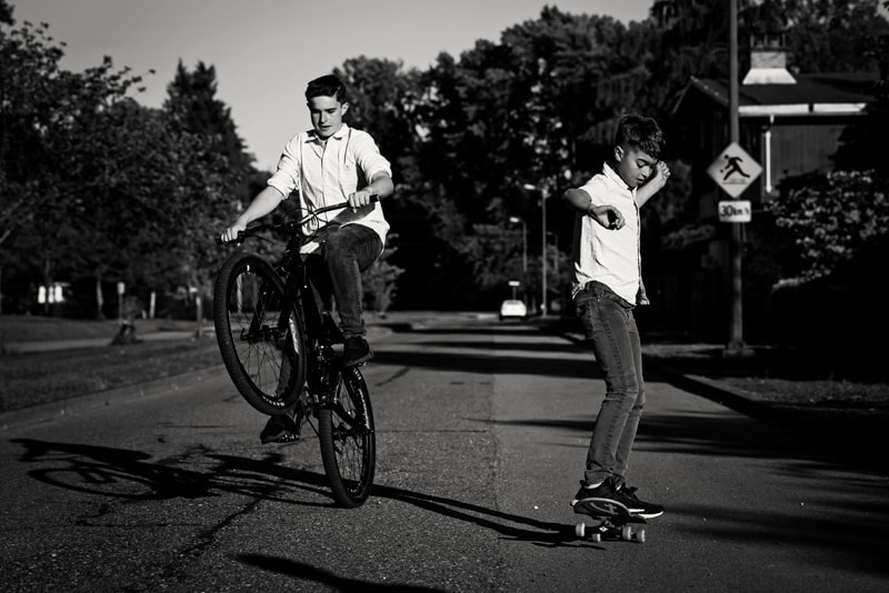 Family Photography, two boys riding a bike and skateboarding