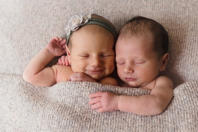 Baby Photography, baby twins tucked in together with a tan blanket